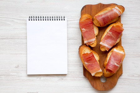 Crostini with serrano ham on rustic wooden board over white wooden background, top view. Blank notepad. Copy space. 스톡 콘텐츠