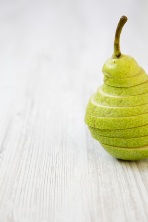 Sliced pear on white wooden background, close-up. Side view. Copy space.