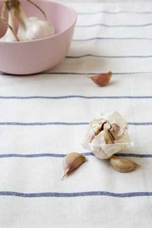 Garlic cloves and garlic bulbs on striped cloth, side view.