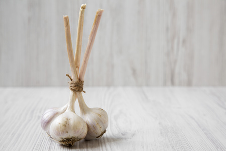 Garlic bulbs on white wooden background, side view. Copy space.