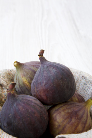 Fresh figs in a bowl on a white wooden surface, side view. Close-up. Space for text.