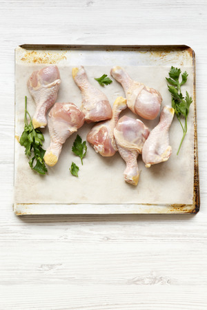 Uncooked chicken legs on a baking sheet paper on tray, high angle view. White wooden background.