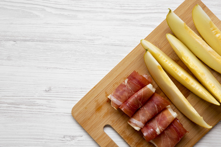 Melon slices with prosciutto on bamboo board over white wooden surface, top view. Overhead, flat lay, from above. Copy space.