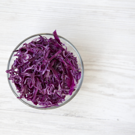Chopped red cabbage in a bowl, closeup. Overhead view.