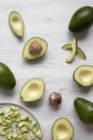 Whole and chopped avocados on white wooden background, high angle view.