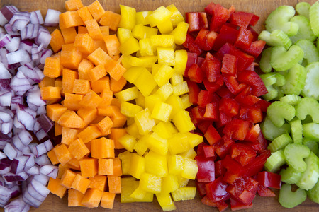 Chopped fresh vegetables (carrot, celery, red onion, peppers) arranged on cutting board, overhead view. Close-up.