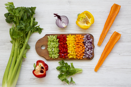 Chopped vegetables (carrot, celery, red onion, peppers) arranged on cutting board on white wooden background, top view. From above, overhead, flat lay.