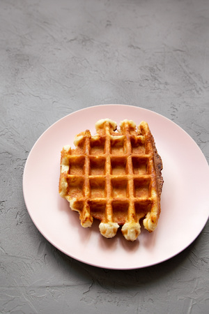 Traditional belgian waffle on pink plate over concrete background, high angle view. Banque d'images