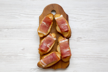 Crostini with serrano ham on wooden board on white wooden table, top view. Flat lay, overhead, from above. Stock Photo