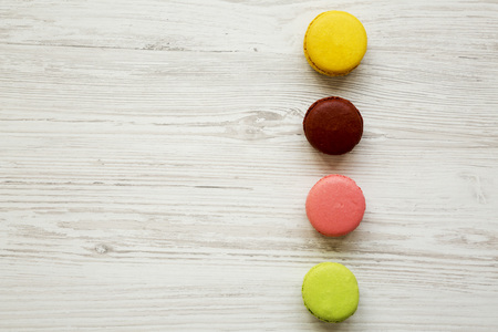 Colorful macaroons on a white wooden background, overhead view. Copy space.