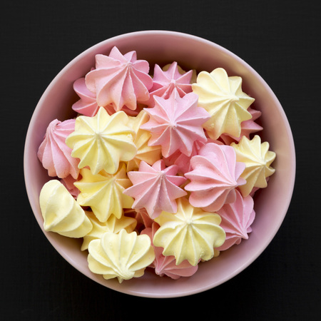 Mini meringues in a pink bowl over black background, top view. From above, overhead, flat lay. Close-up.