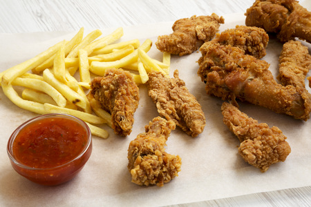 Delicious fast food: fried chicken legs, spicy wings, French fries and chicken fingers with sour-sweet sauce on baking sheet over white wooden background, close-up.