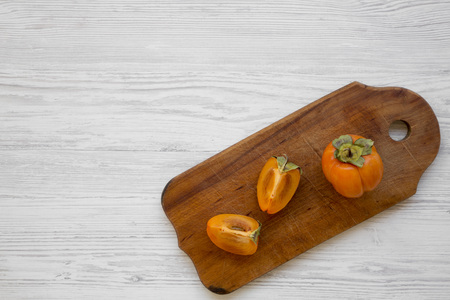 Fresh persimmon on a chopping board on white wooden table, overhead view. Flat lay, top view, from above. Copy space. Stockfoto