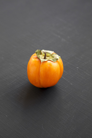 Fresh persimmon on black background, side view. Close-up.