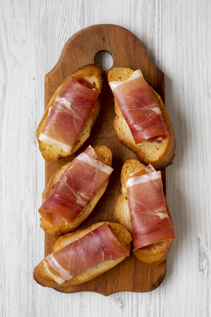 Crostini with serrano ham on rustic wooden board on white wooden table, top view. Flat lay, overhead, from above. Closeup. Stock Photo