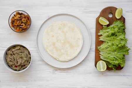 Shrimp taco ingredients on white wooden table, overhead view. Flat lay, top view, from above.
