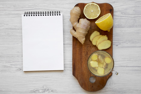 Mug of homemade ginger tea with lemon on wooden board, blank notepad over white wooden background, top view. Copy space. 免版税图像