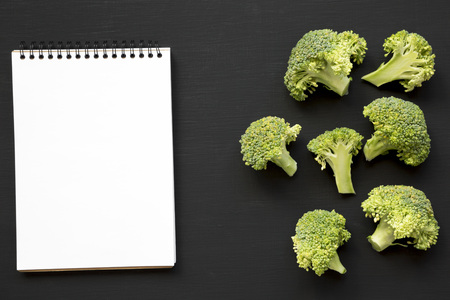 Raw broccoli and blank notebook on black background, overhead view. From above, flat lay. Space for text.