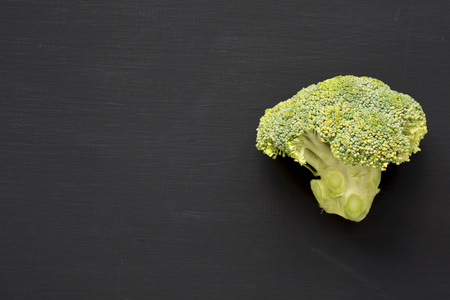 Raw broccoli on black background, top view. Flat lay, from above. Copy space. Stockfoto
