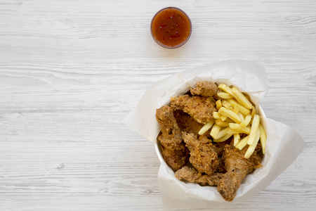 Tasty fastfood: fried chicken drumsticks, spicy wings, French fries and chicken strips in paper box, sauce on a white wooden background, overhead view. Flat lay, top view, from above. Copy space. Stock Photo