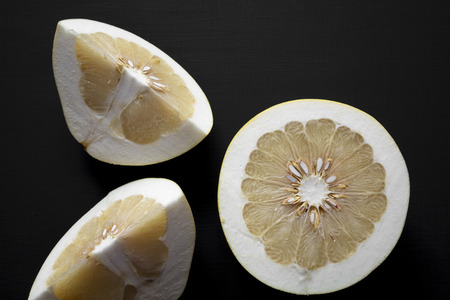 Sliced pomelo on black background, top view.