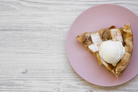 Fetta di torta di mele fatta in casa con gelato sul piatto rosa. Fondo di legno bianco. Copia spazio. Disteso piatto, sopra la testa, dall'alto. Archivio Fotografico