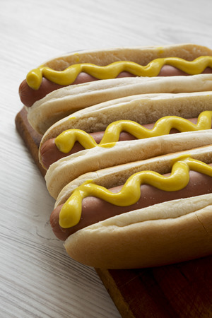 Hot dog with yellow mustard on wooden board on white wooden table, side view. Closeup.