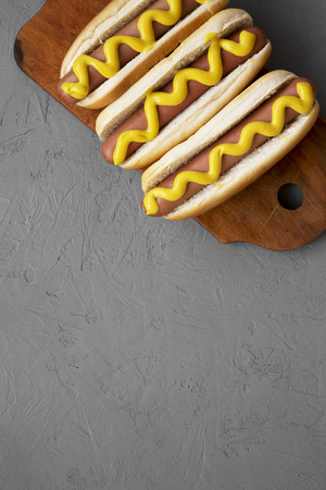 Tasty hot dogs with yellow mustard on wooden board on grey background, overhead view. Copy space.