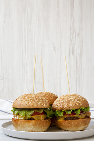 Homemade cheeseburgers on grey plate on white wooden background, side view. Closeup. Imagens