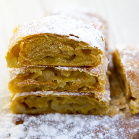 Strudel or apple pie on rustic wooden board. Close up. 免版税图像