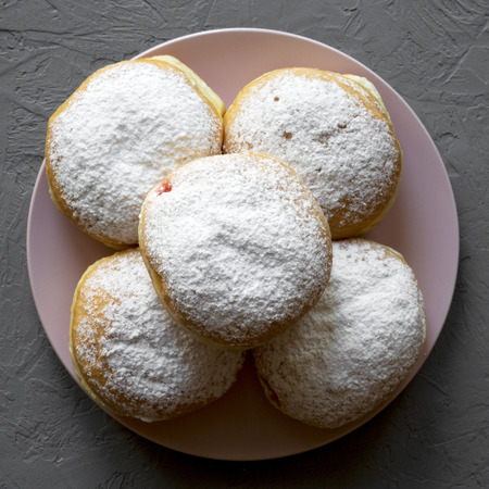 Homemade tasty donuts with powdered sugar on pink plate over concrete background, top view. Flat lay, overhead.
