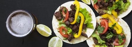 Tasty tacos with beef and vegetables, beer and lime on a black surface, overhead view. Mexican kitchen. Flat lay, top view, from above. Stock Photo