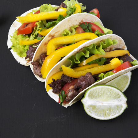 Tacos with beef and vegetables and lime on a black surface, side view. Close-up.