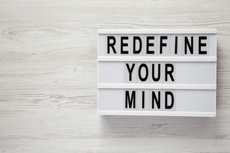 'Redefine your mind' words on lightbox over white wooden surface, top view. Overhead, flat lay, from above. Copy space.