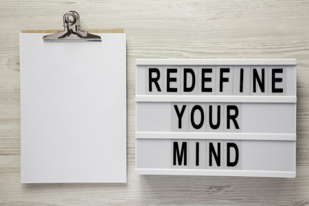Redefine your mind words on modern board, noticepad over white wooden background, top view. Overhead, flat lay, from above.