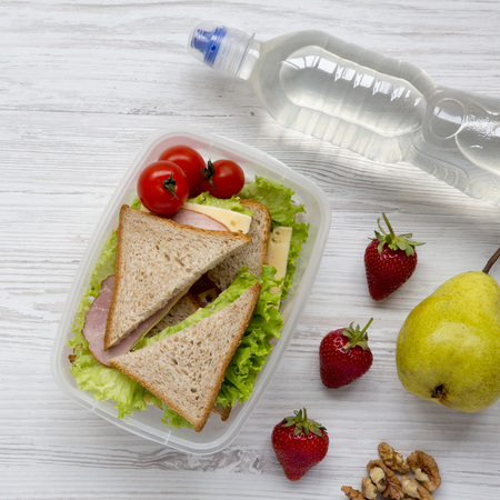 Healthy school lunch box with fresh organic vegetables sandwiches, walnuts, bottle of water and fruits on white wooden surface, overhead view. From above, top view.