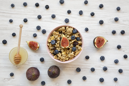 Pink bowl of fruit granola with fruits and honey, top view. Flat lay, from above, overhead. Close-up. Archivio Fotografico