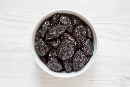 Full bowl of dry prunes on a white wooden surface, top view. Overhead, flat lay, from above.