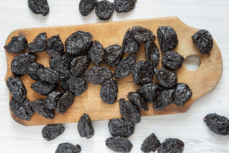 Dry prunes on rustic wooden board on a white wooden background, overhead view. Flat lay, from above, top view.