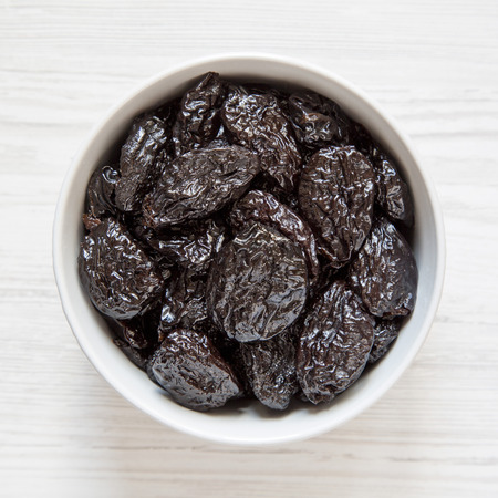 Full bowl of dry prunes on a white wooden background, top view. Overhead, flat lay, from above. Archivio Fotografico