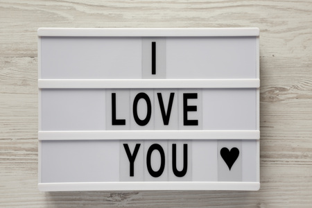 Modern board with text 'I Love You' on a white wooden background, top view. Flat lay, overhead. Valentine's Day 14 February.