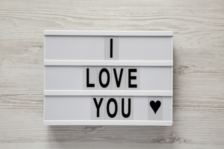 Lightbox with text 'I Love You' on a white wooden background, top view. Flat lay, overhead. Valentine's Day 14 February.