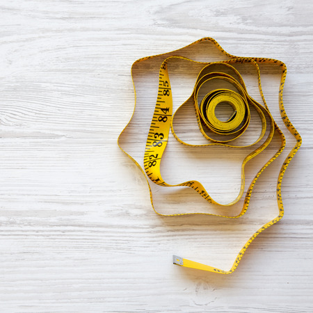 Yellow measuring tape on a white wooden background, top view. Space for text. 版權商用圖片