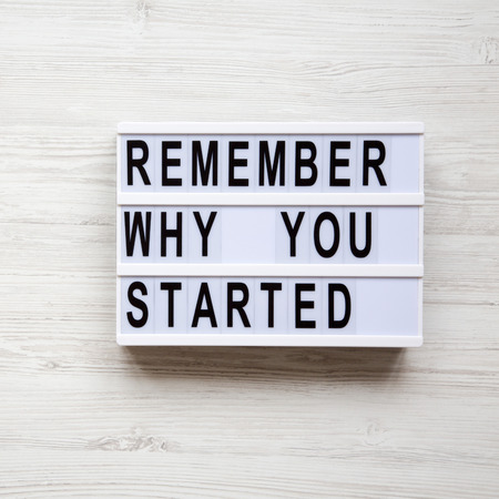 Modern board with text 'Remember why you started' over white wooden background, top view. Overhead, from above.
