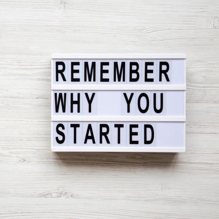 """Moderne Tafel mit Text """"Erinnern Sie sich daran, warum Sie angefangen haben"""" auf weißem Holzhintergrund, Ansicht von oben. Oben, von oben."""
