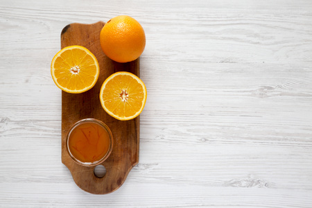 Homemade orange marmelade on rustic board on a white wooden table, top view. Flat lay, overhead, from above.  Zdjęcie Seryjne