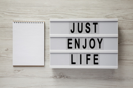 Modern board with text Just enjoy life, blank notepad on a white wooden table, top view. Copy space.