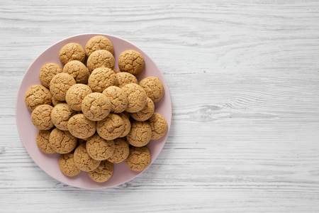 Almond cookies on pink plate over white wooden background, top view. Flat lay, overhead, from above. Copy space.