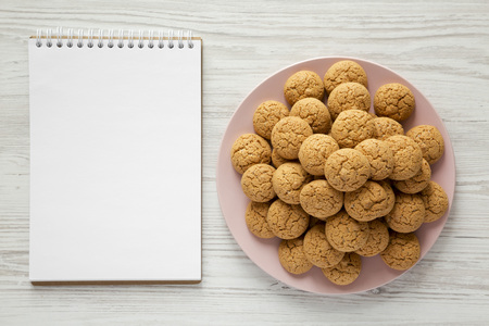 Almond cookies on pink plate, blank notebook over white wooden background, top view. Flat lay, overhead, from above.