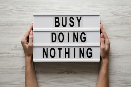 Female hands hold modern board with text 'Busy doing nothing' over white wooden surface, top view. From above, flat lay, overhead.